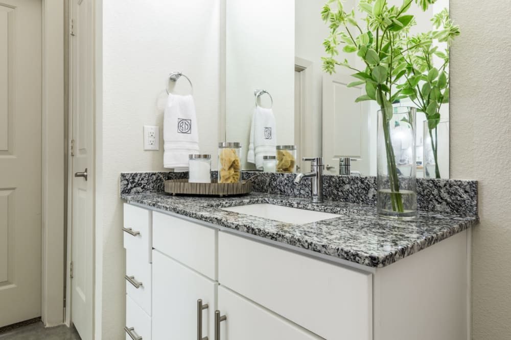 Granite counter bathroom sink with white cabinets and mirror at Marq on Burnet in Austin, Texas