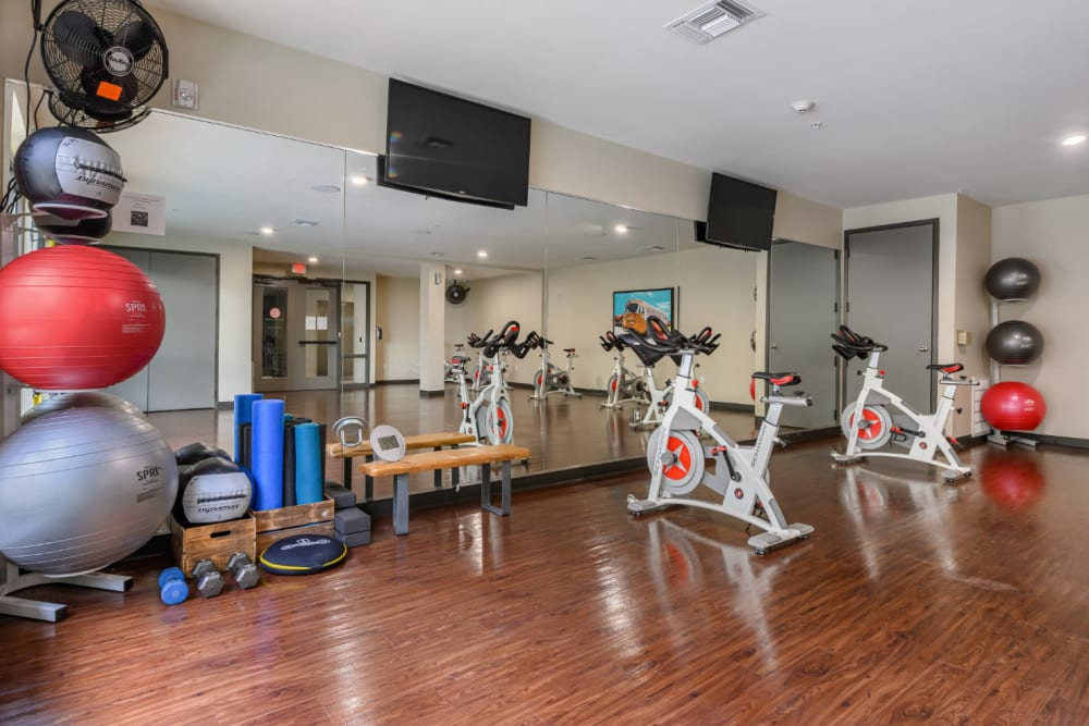 Spin bikes facing mirrors in separate fitness room at The 704 in Austin, Texas