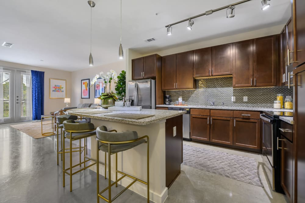 Spacious kitchen with granite counter island and stool chairs at The 704 in Austin, Texas