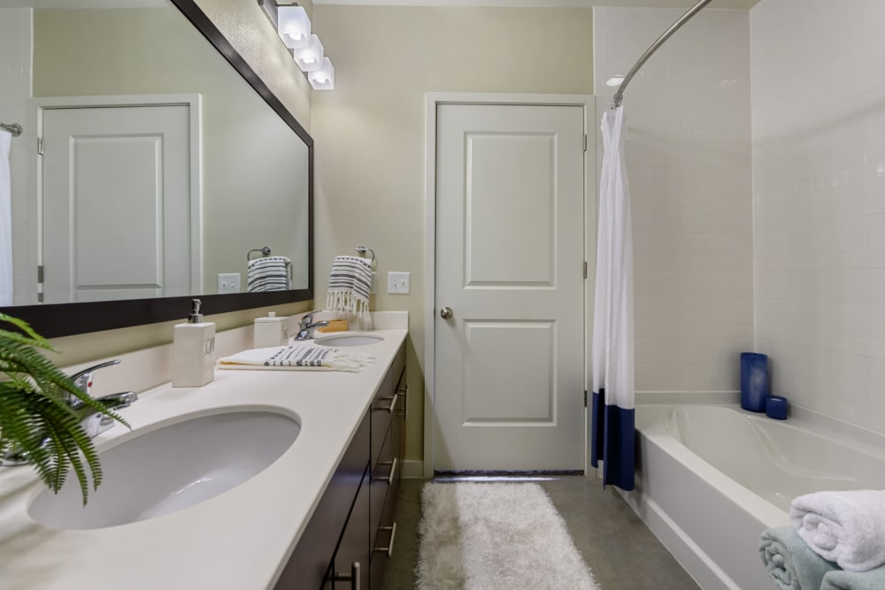 Bright bathroom with double sinks, concrete flooring, and bathtub at The 704 in Austin, Texas