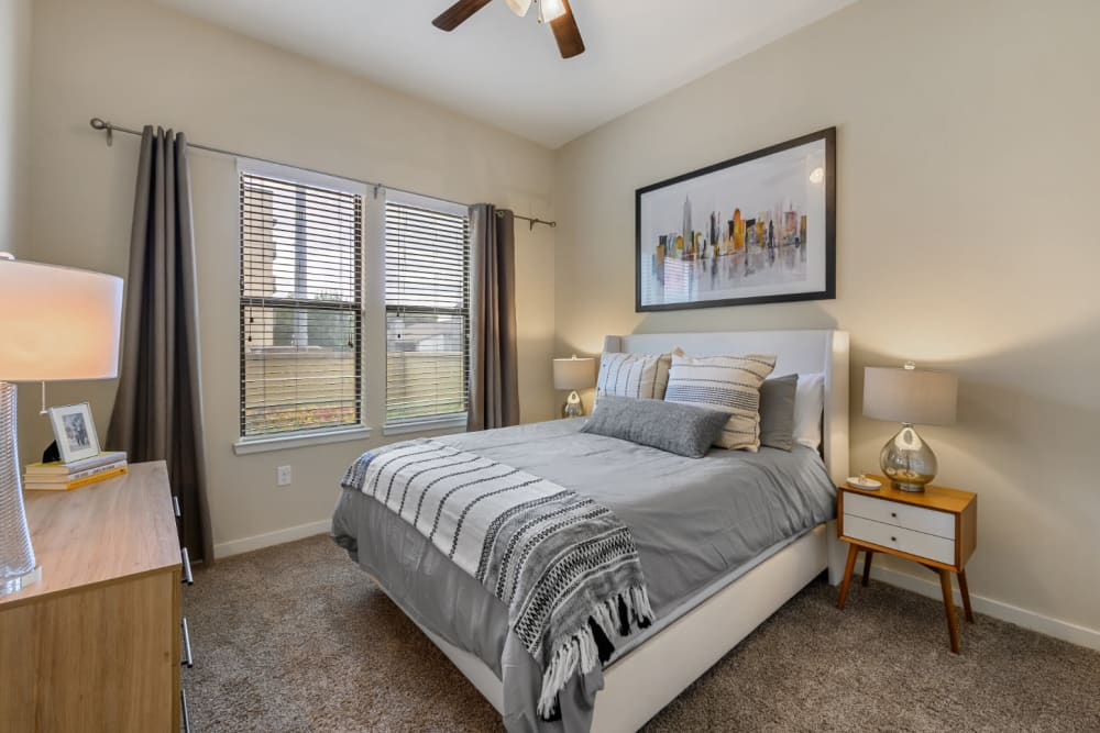 Carpeted bedroom with large bed, side tables, dresser, and windows at The 704 in Austin, Texas