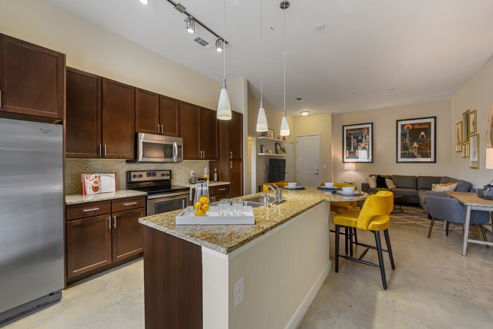Spacious and open floor plan with kitchen, dining, desk, and living room areas at The 704 in Austin, Texas