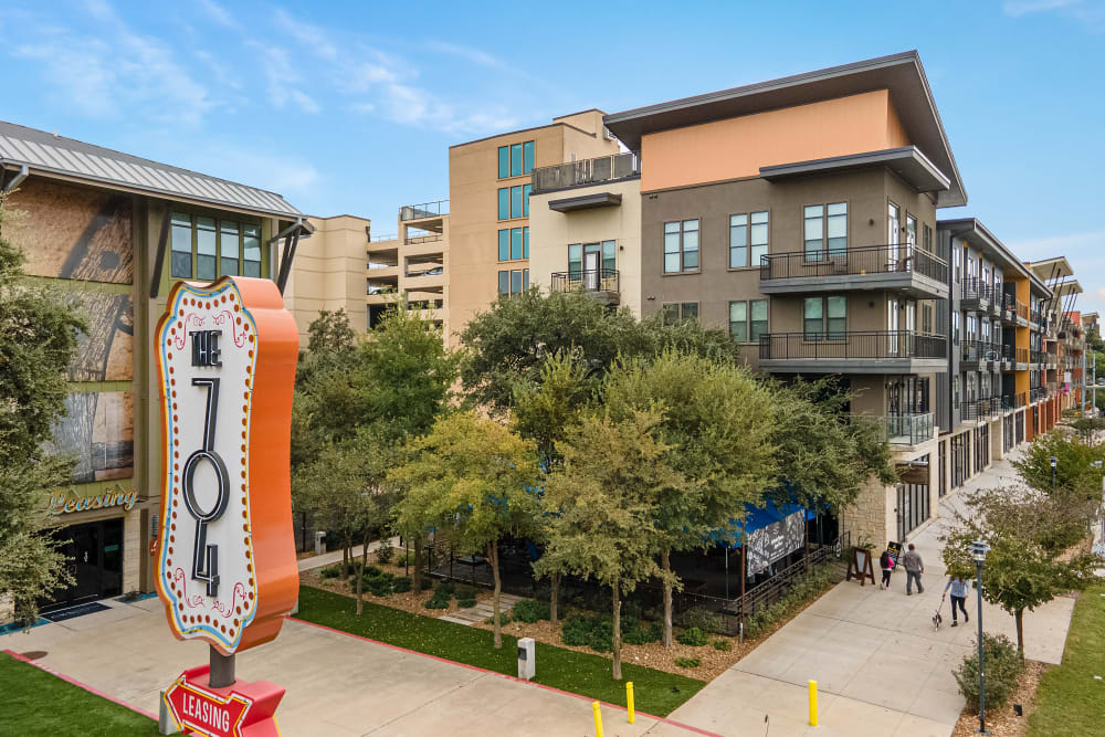 Aerial view of vintage sign and leasing office entrance of at The 704 in Austin, Texas