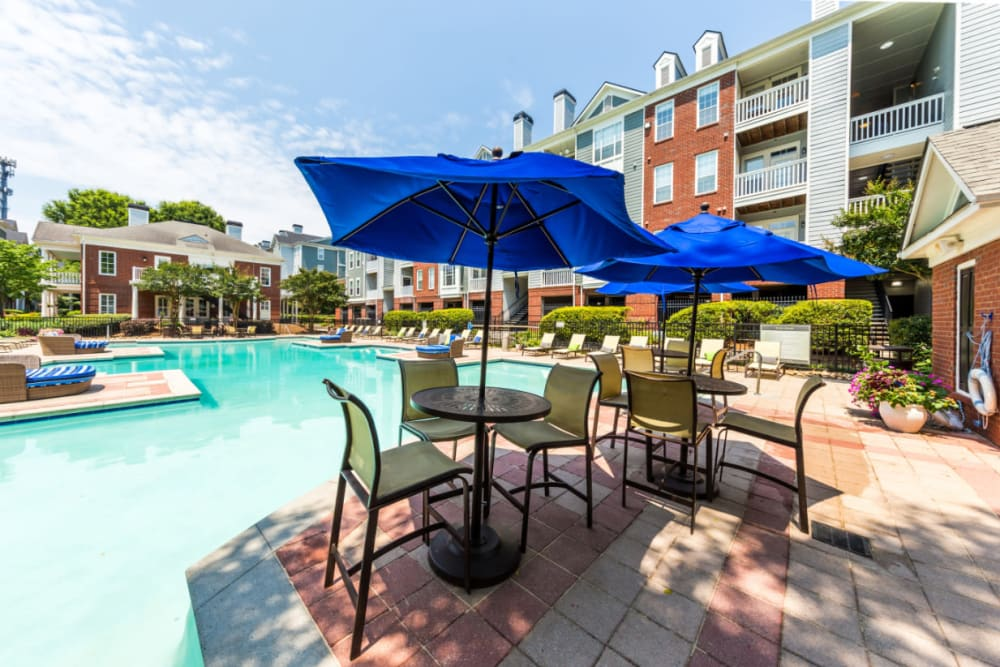 Umbrella covered dining tables and chairs on pool deck at The Marq at Brookhaven in Atlanta, Georgia