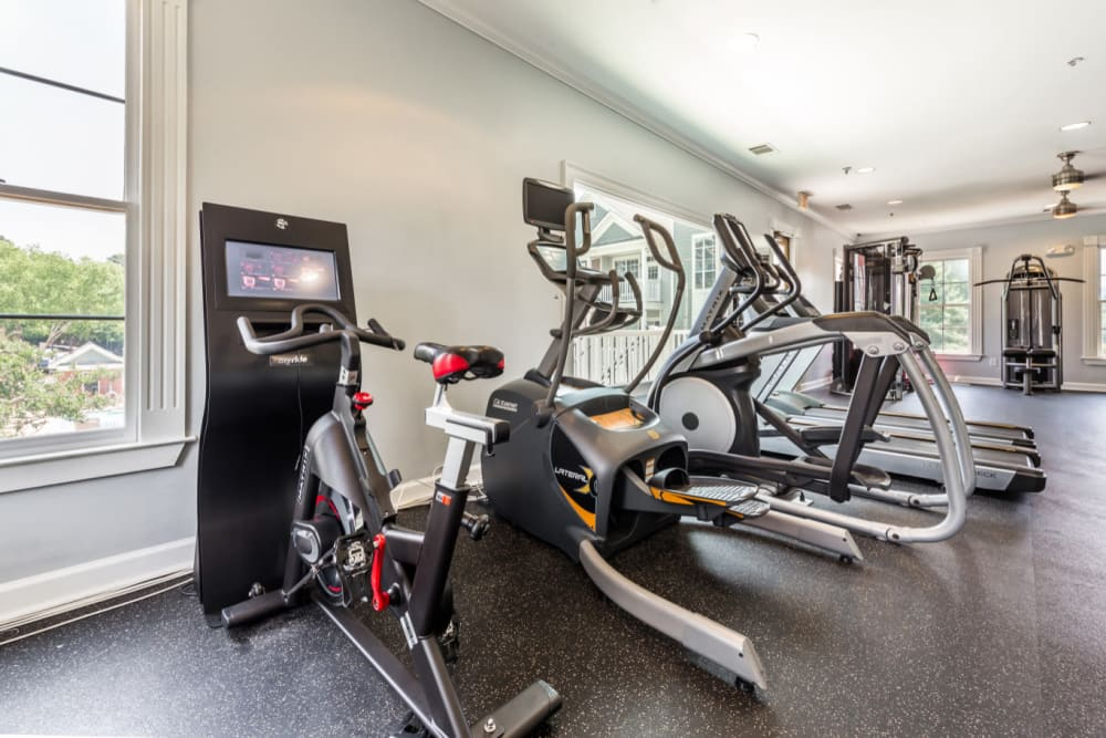 Spin bike with personal monitor next to elliptical machines in fitness room at The Marq at Brookhaven in Atlanta, Georgia