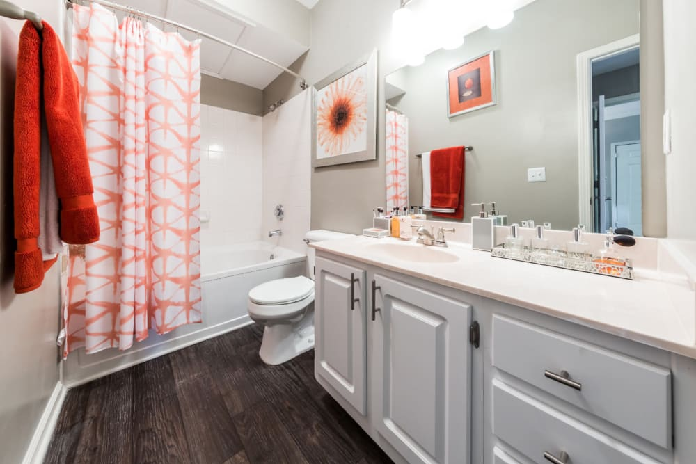 Bright bathroom with white cabinets and wood flooring at The Marq at Brookhaven in Atlanta, Georgia