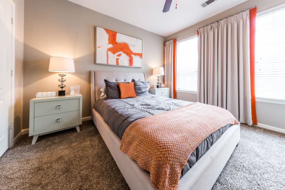 Carpeted master bedroom with large bed, side tables, and large windows at The Marq at Brookhaven in Atlanta, Georgia