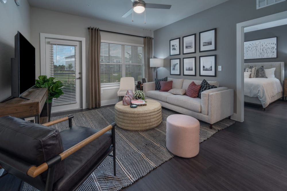 Living room area with wood style flooring and private patio access at Reunion at 400 in Kissimmee, Florida