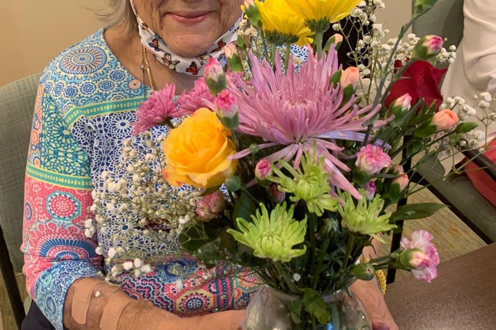 Female resident smiling and holding flowers enjoying life at Azpira at Windermere