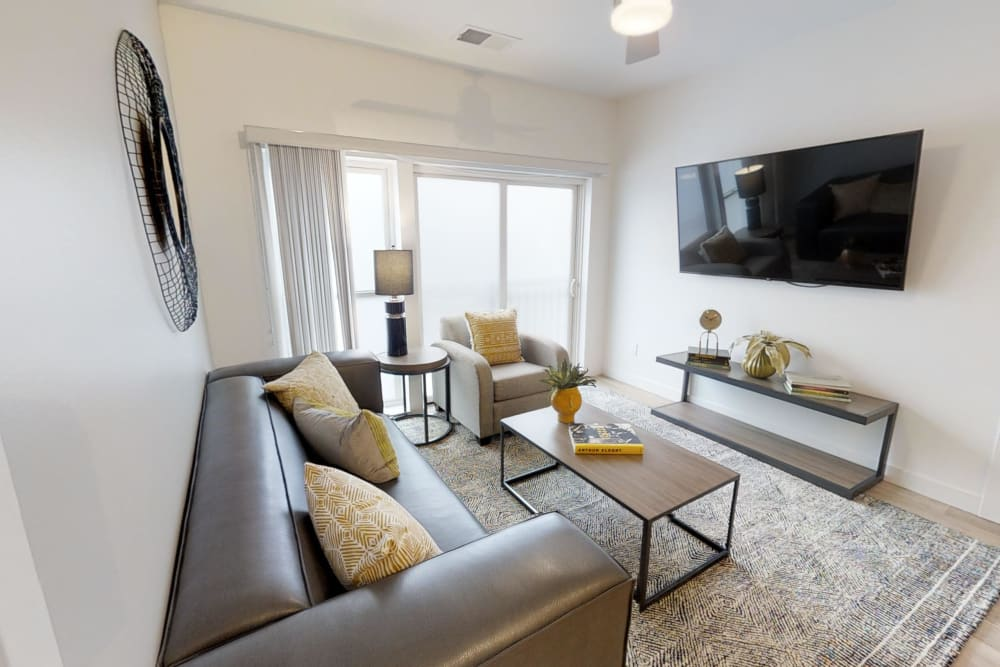 Cozy bright living room with a mounted tv in a furnished apartment at The View on Pavey Square in Columbus, Ohio