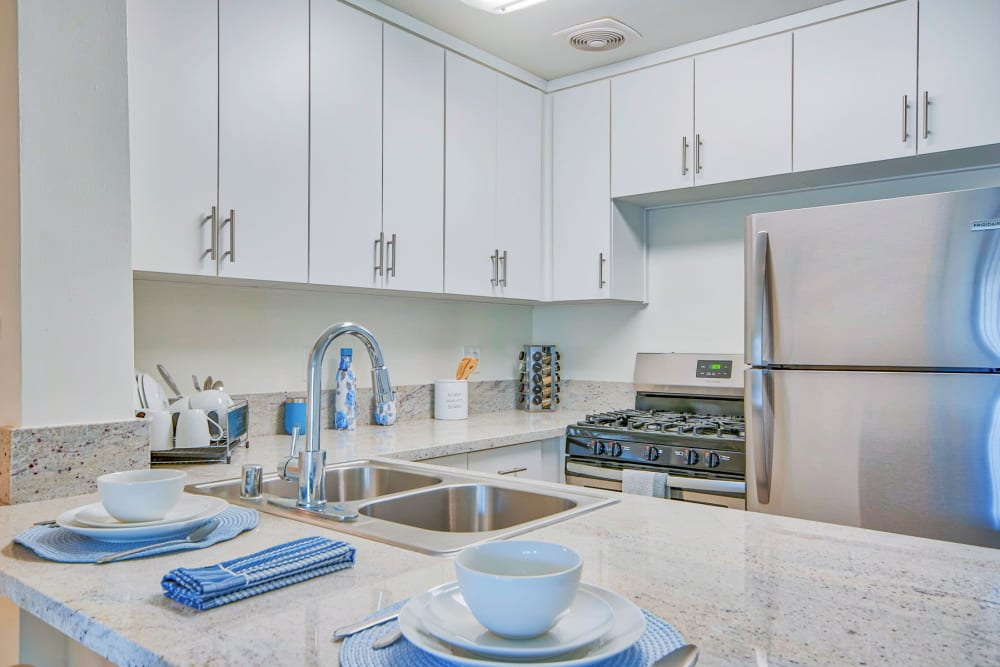 Dual-basin sink and stainless-steel appliances in a model apartment's kitchen at Villa Vicente in Los Angeles, California