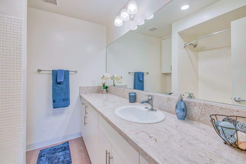 Large vanity mirror and a granite countertop in a model home's bathroom at Villa Vicente in Los Angeles, California