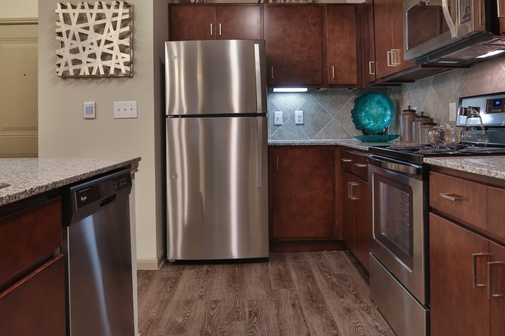 Model apartment kitchen with stainless steel appliances at Olympus at Waterside Estates in Richmond, Texas