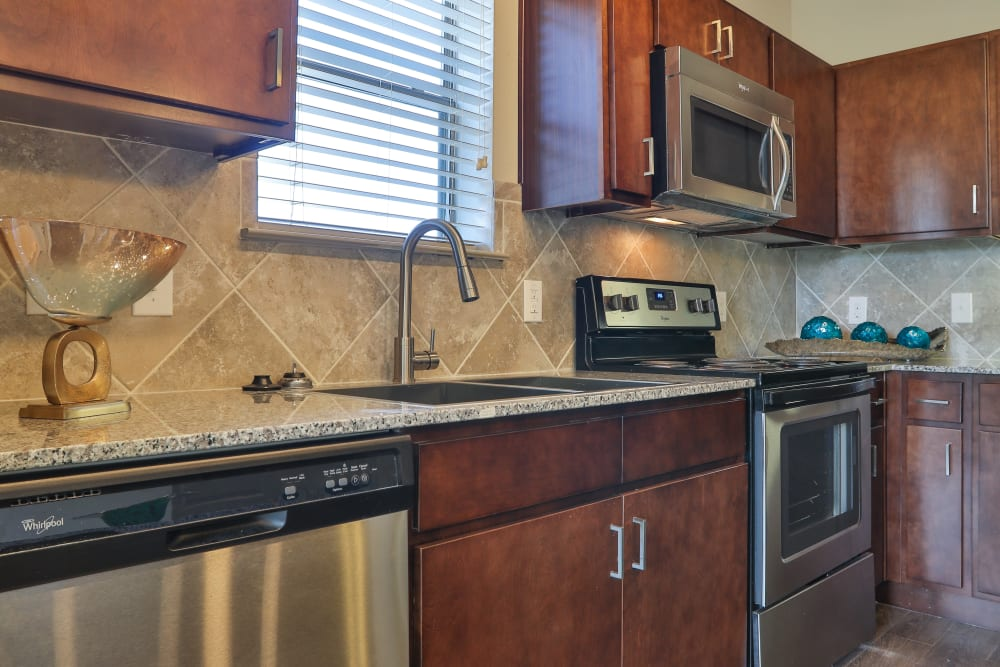 Kitchen with modern black appliances and sink at Olympus at Waterside Estates in Richmond, Texas