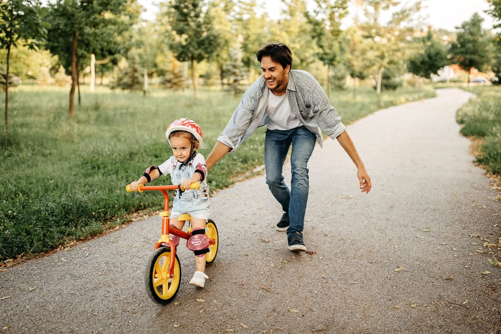 Father pushing his kid on their bike near The Galaxy in Silver Spring, Maryland