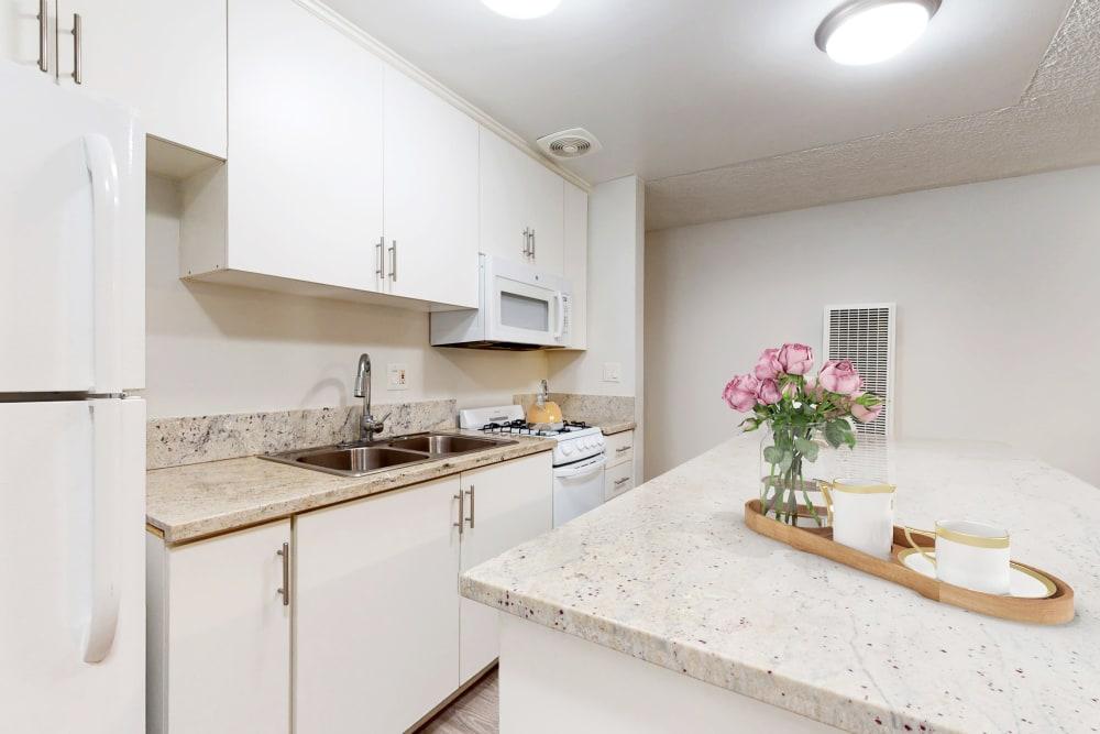 Kitchen with island in a studio apartment at Casa Granada in Los Angeles, California