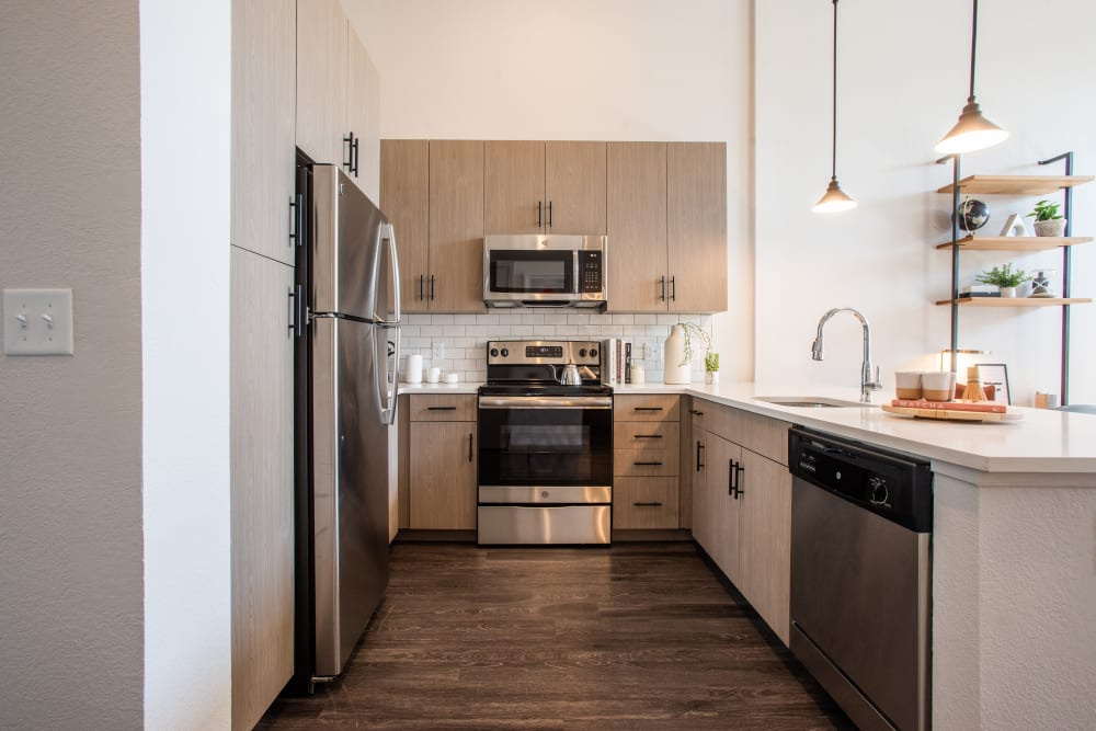 Kitchen with wood style flooring at Marq Iliff Station in Aurora, Colorado