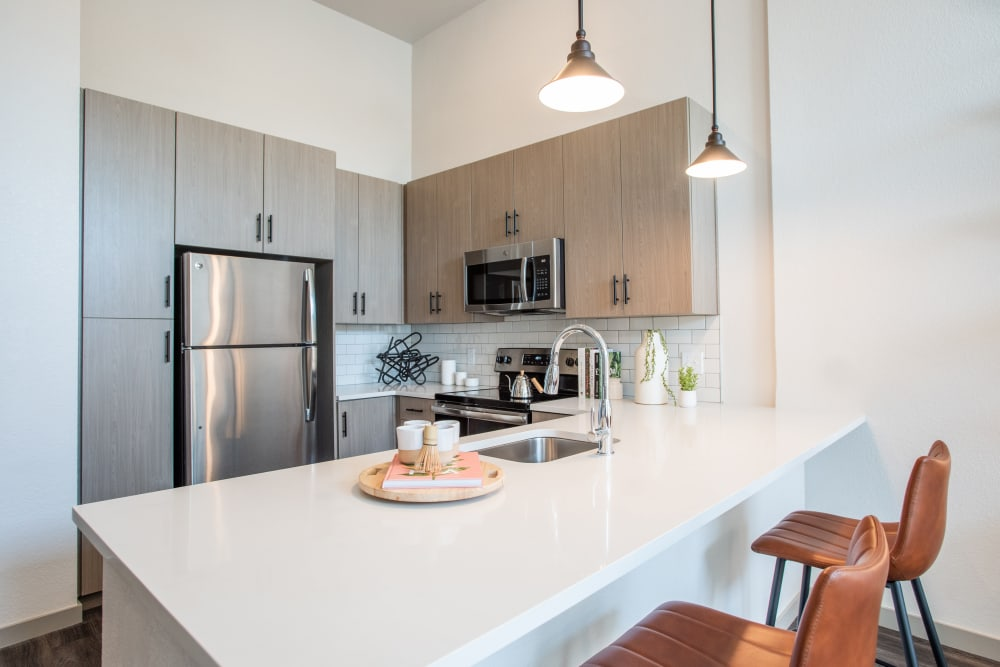 Kitchen with stainless steel appliances at Marq Iliff Station in Aurora, Colorado