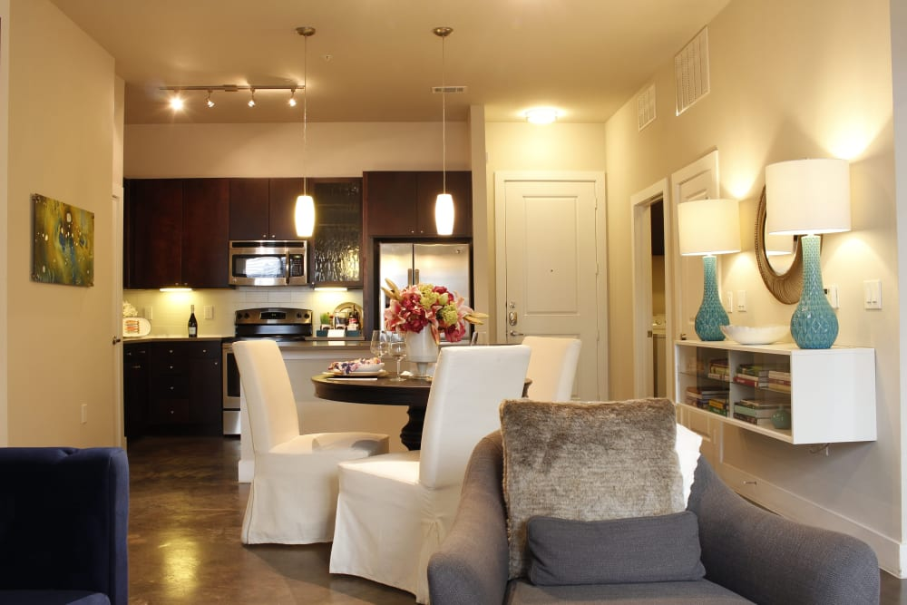 Dining and kitchen area in a well lit home at Macallan at Ross in Dallas, Texas