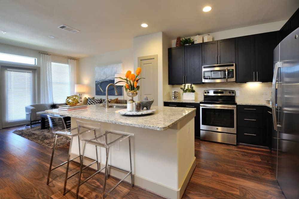 Granite counter island with bar stool chairs and stainless steel appliances in kitchen at Olympus Falcon Landing in Katy, Texas