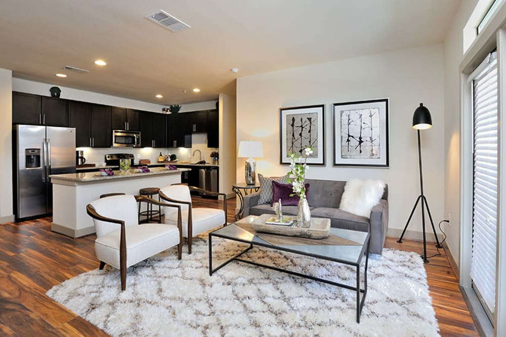 Model living room with wood flooring at Olympus Falcon Landing in Katy, Texas