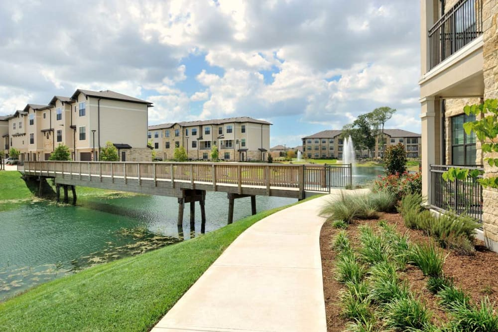 Scenic walkway along lake and building units at Olympus Falcon Landing in Katy, Texas
