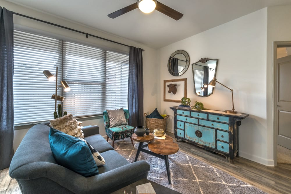 Cozy living room with large windows bringing in tons of natural light at Mercantile River District in Fort Worth, Texas