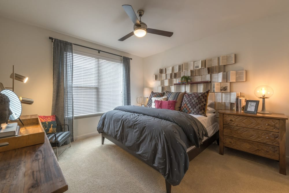 Well lit bedroom with ceiling fan and carpet at Mercantile River District in Fort Worth, Texas