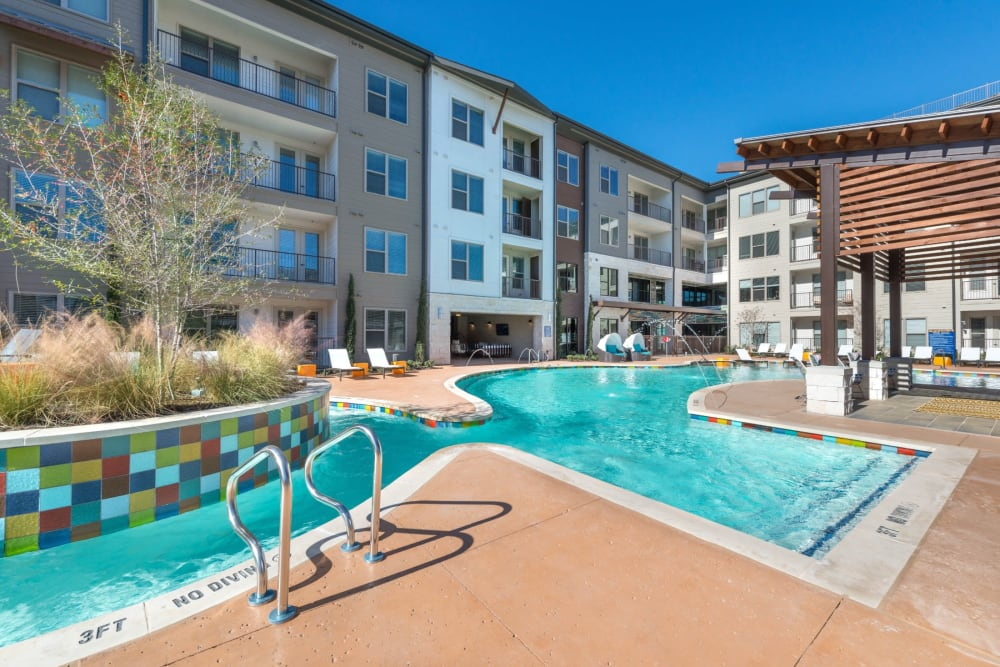 Resort style swimming pool with a walk in edge at Mercantile River District in Fort Worth, Texas