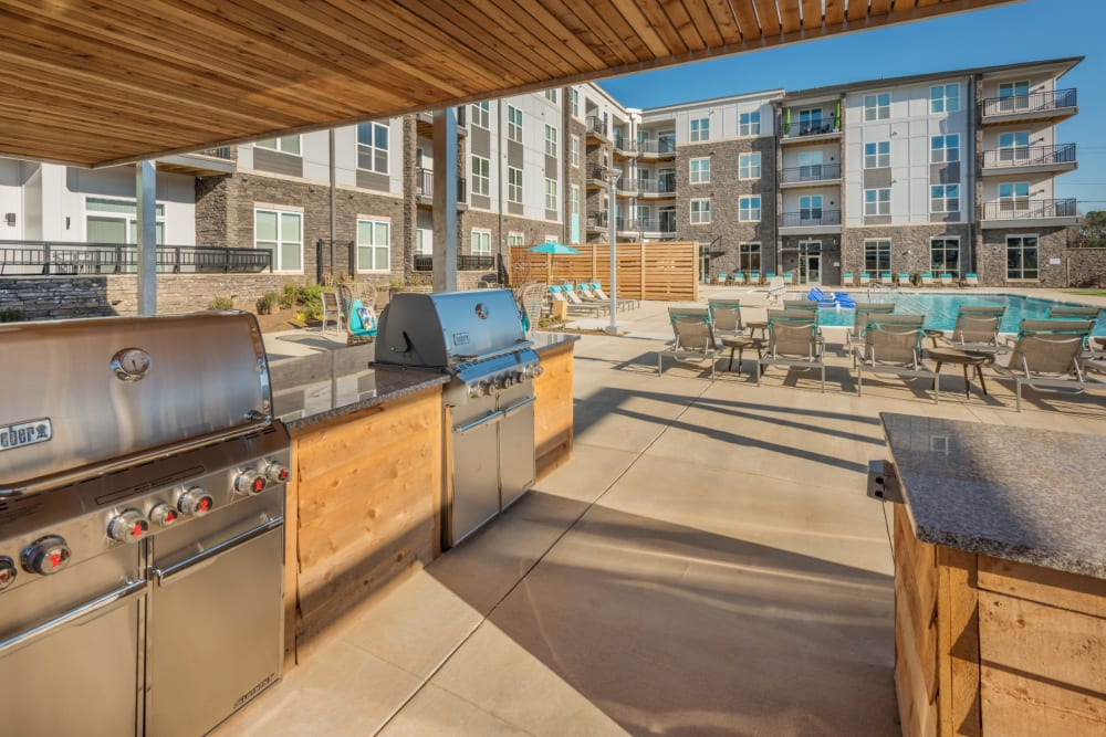 Grilling area next to the pool with tons of space to cook, eat, and relax at Blu at Northline Apartments in Charlotte, North Carolina