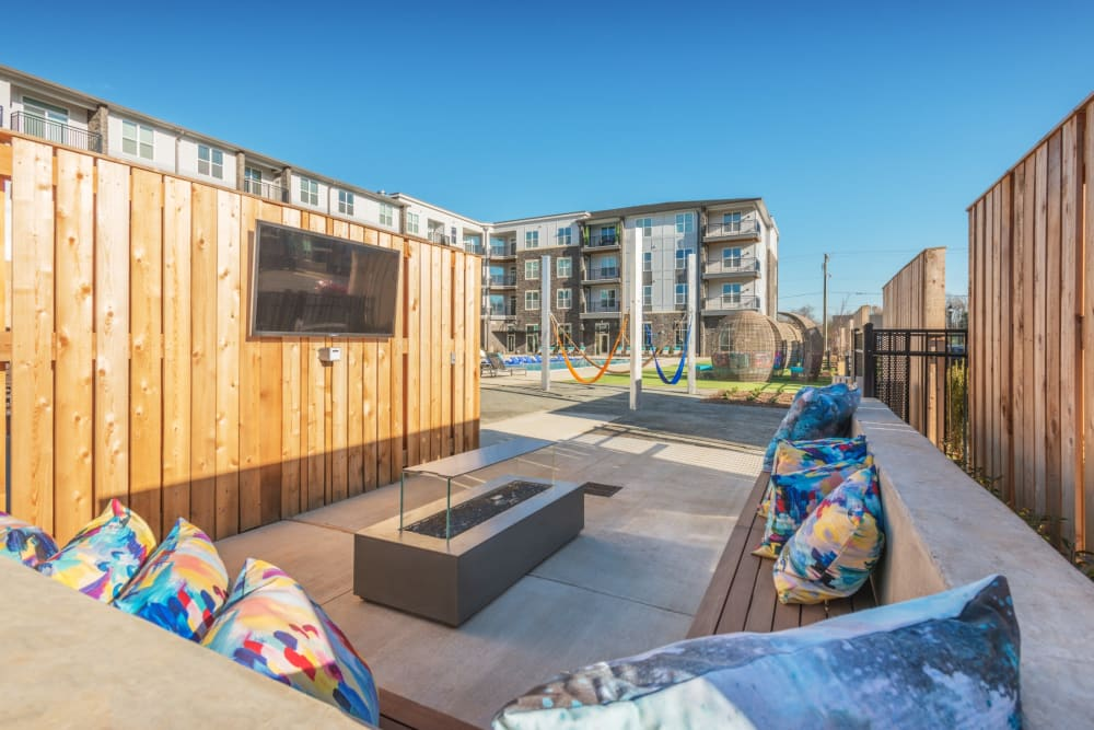Big outdoor couch and firepit with a tv mounted on the wall at Blu at Northline Apartments in Charlotte, North Carolina