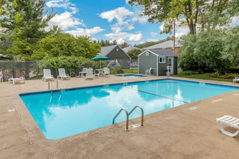 Beautiful blue pool with lounge chairs at Eagle Rock Apartments at Nashua in Nashua, New Hampshire