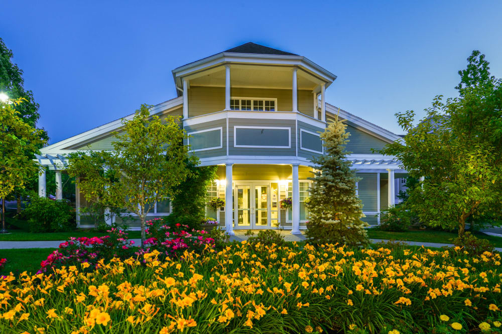 Clubhouse and leasing center entrance with grand flower bed in front at Sofi Danvers in Danvers, Massachusetts