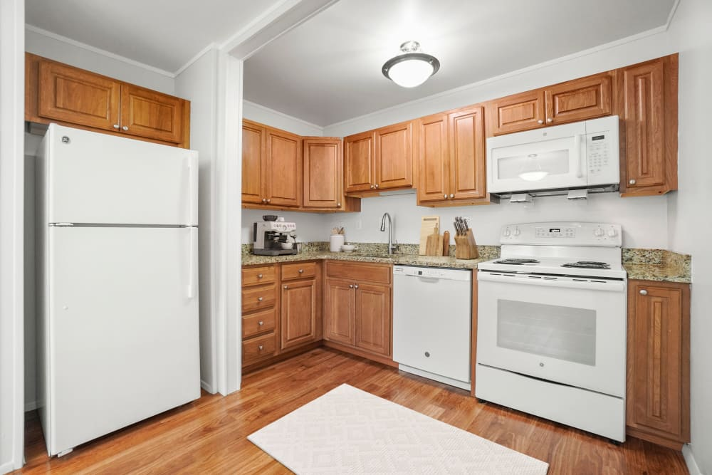 Kitchen with white appliances at Taunton Gardens in Taunton, Massachusetts