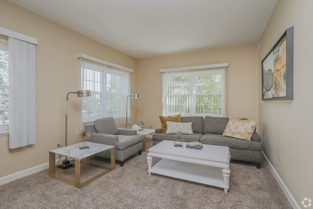 Senior apartment living room with a chair, couch, and white coffee tables at Hanover Place in Tinley Park, Illinois