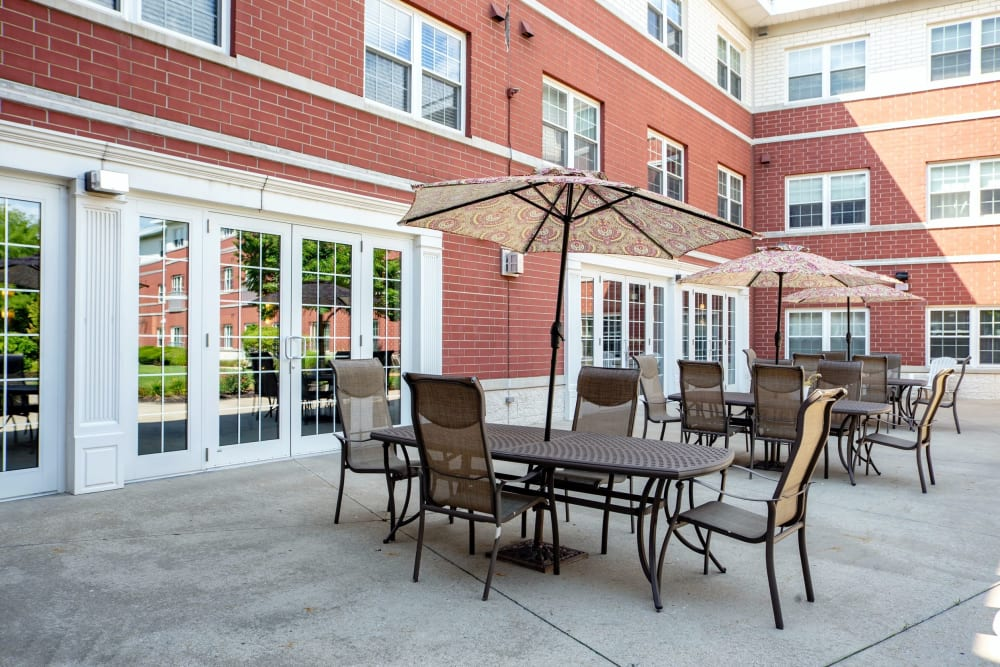 Outdoor shaded tables on the patio at Hanover Place in Tinley Park, Illinois