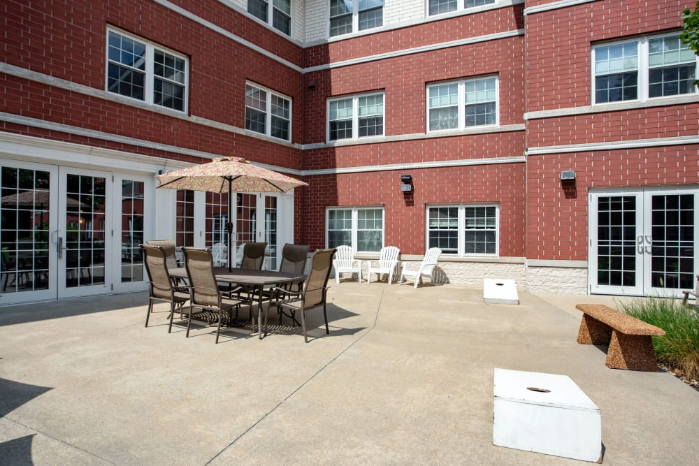 Paved patio with seating and games at Hanover Place in Tinley Park, Illinois