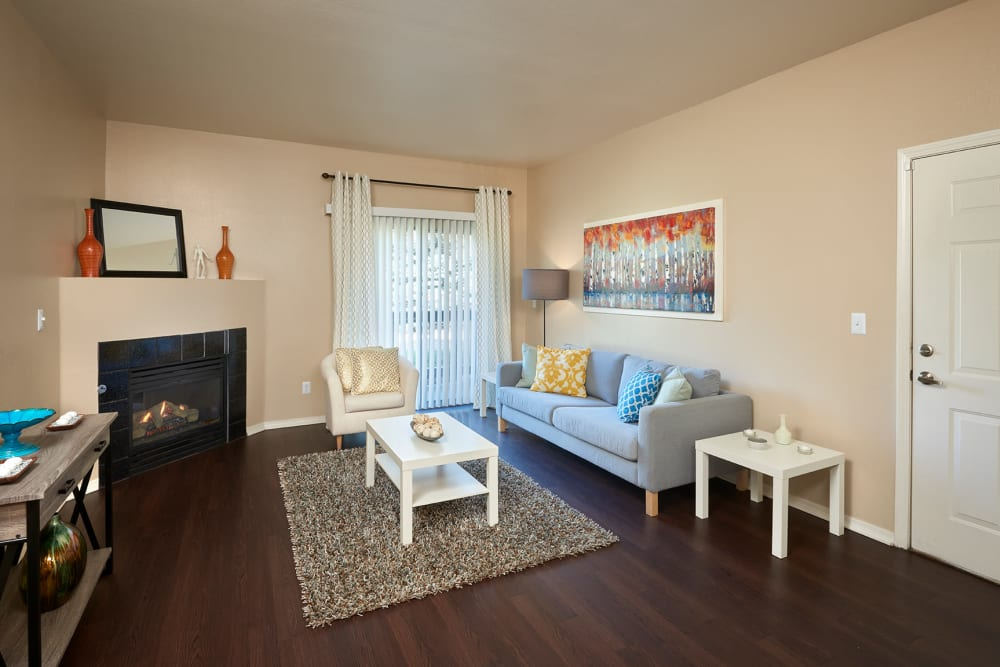 A living room complete with a fireplace at Crossroads at City Center Apartments in Aurora, Colorado