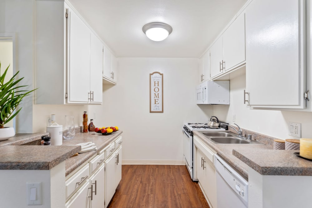 Bright kitchen with white appliances and wood flooring at The Diplomat in Studio City, CA