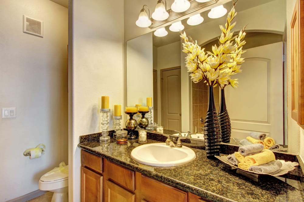 Barthroom with large vanity mirror and marble countertops at Marquis at The Woodlands in Spring, Texas