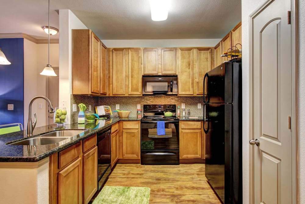 Large open kitchen with plenty of wooden cabinets at Marquis at The Woodlands in Spring, Texas