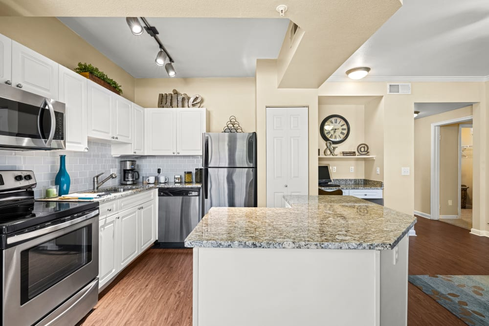 Open the kitchen with white cabinets and marble countertops at Marquis at Town Centre