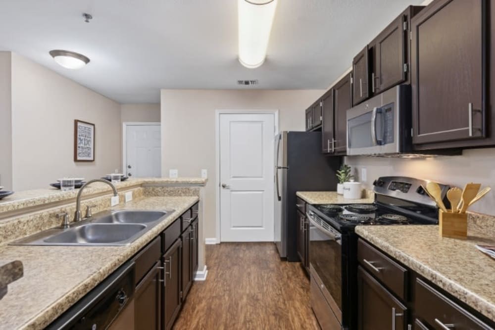 Kitchen with dark brown cabinetry and  granite countertops at Marquis on Cary Parkway