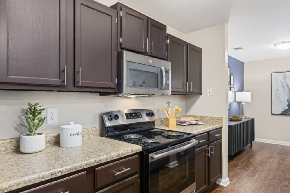 Kitchen with dark brown cabinetry and marble countertops at Marquis on Cary Parkway