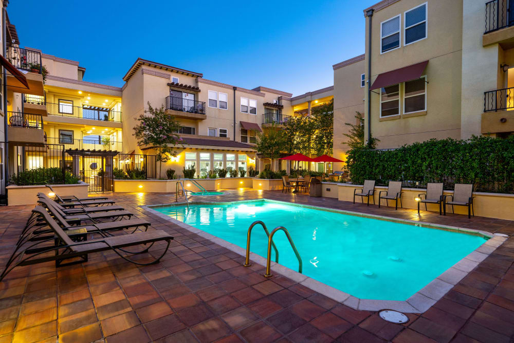 Pool surrounded by lounge chairs and units at sunset at The Villagio in Northridge, CA