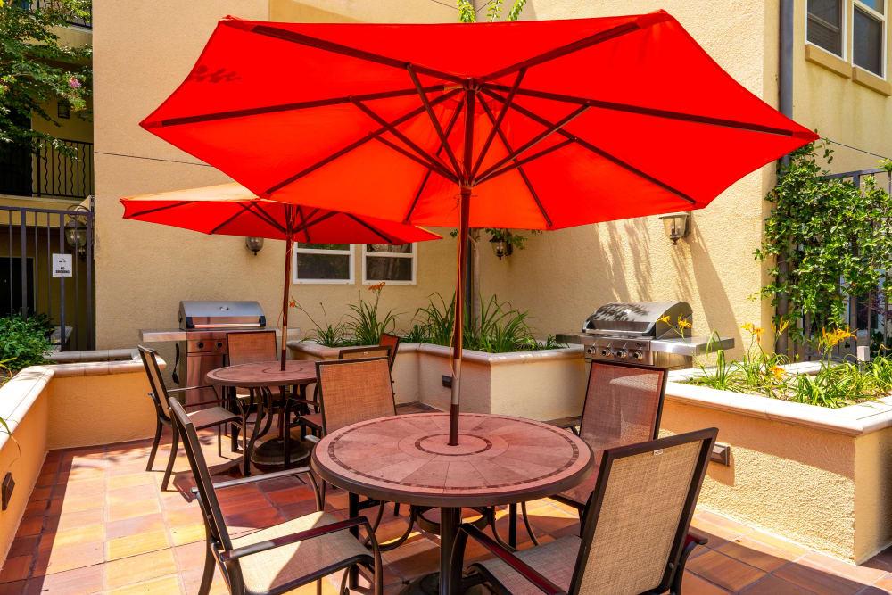 Poolside BBQ with umbrella covered tables and chairs at The Villagio in Northridge, CA