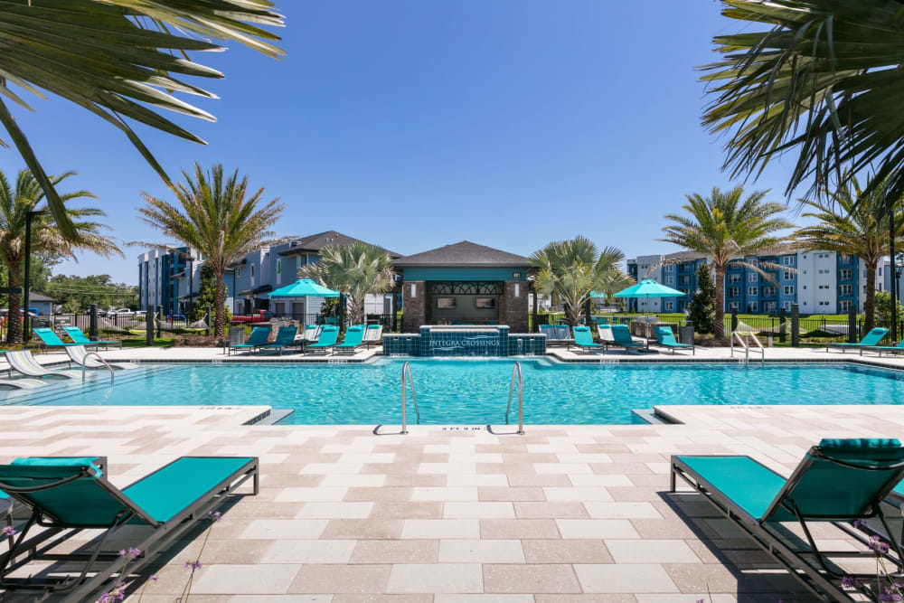 Pool with sun chairs at Integra Crossings in Sanford, Florida
