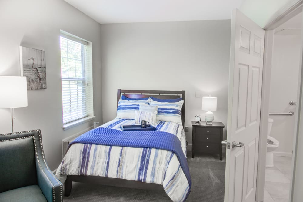 Well lit bedroom with colorful comforter at Truewood by Merrill, Riverchase in Hoover, Alabama.