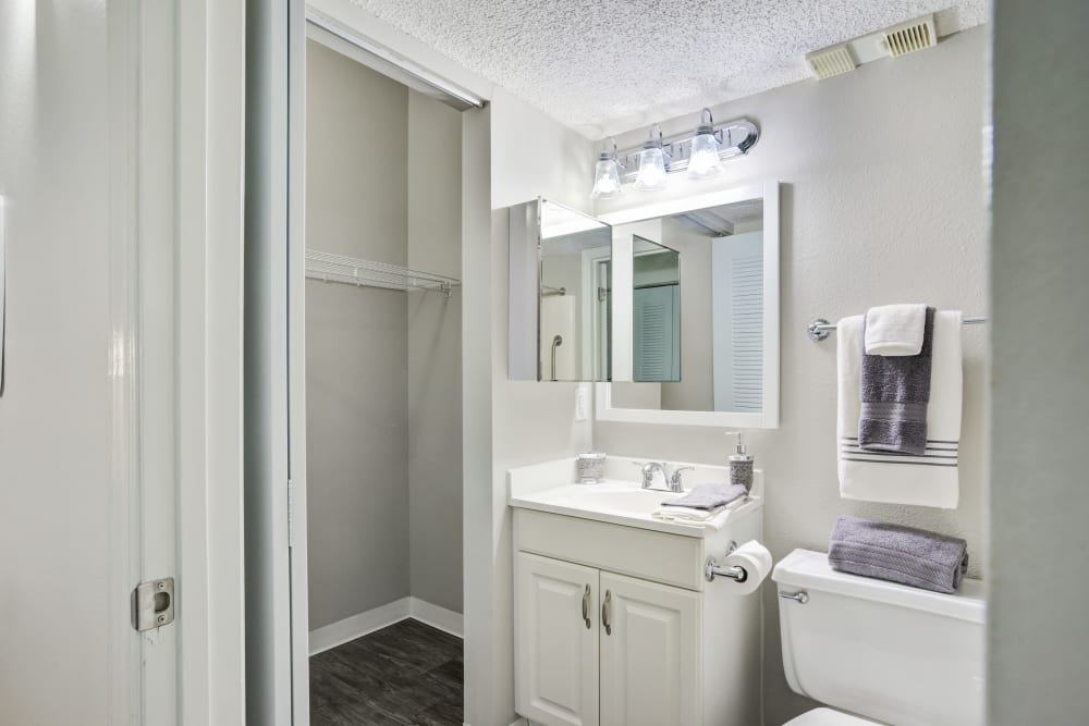 Bathroom featuring large vanity mirror and white finishes in an apartment at Truewood by Merrill, Port Charlotte in Port Charlotte, Florida.