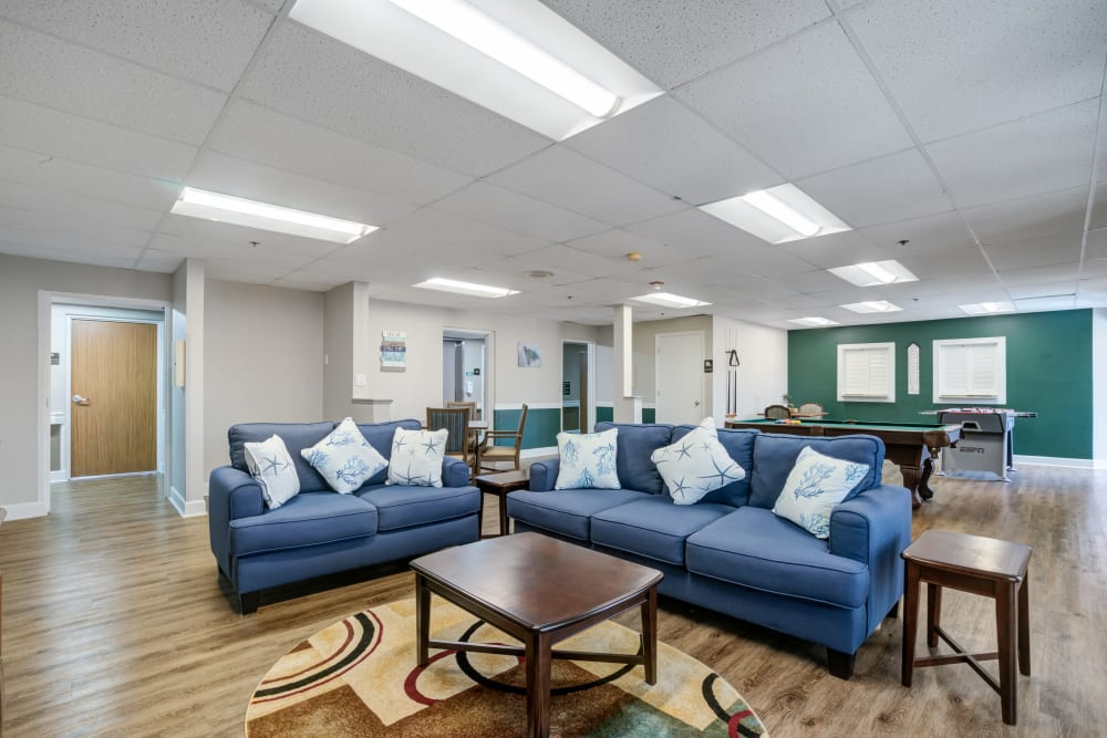Comfortable couch sitting area in community space at Truewood by Merrill, Port Charlotte in Port Charlotte, Florida.